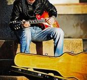 Gitarrspelare med ett öppet gitarrfall Royaltyfri Foto