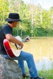 Gitarrspelare på dammet arkivfoto