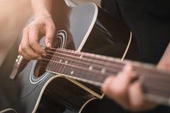 Gitarrspelare som spelar den akustiska gitarren, slut upp Arkivbild