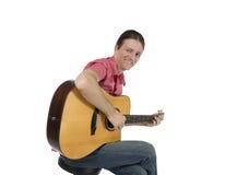 Gitarrspelare som spelar hans akustiska gitarr med ett leende Arkivfoto
