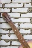 Gitary akustycznej headstock przeciw białemu ściana z cegieł Fotografia Stock