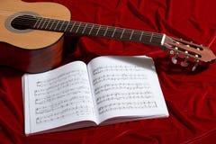 Gitary akustycznej i muzyki notatki na czerwonej aksamitnej tkaninie, zamknięty widok przedmioty Zdjęcie Stock
