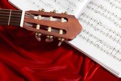 Gitary akustycznej i muzyki notatki na czerwonej aksamitnej tkaninie, zamknięty widok przedmioty Zdjęcia Royalty Free