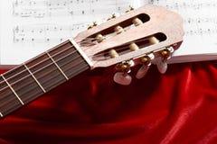 Gitary akustycznej i muzyki notatki na czerwonej aksamitnej tkaninie, zamknięty widok przedmioty Zdjęcia Stock
