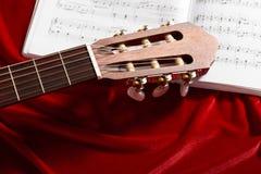 Gitary akustycznej i muzyki notatki na czerwonej aksamitnej tkaninie, zamknięty widok przedmioty Obrazy Royalty Free