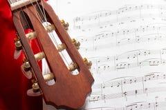 Gitary akustycznej i muzyki notatki na czerwonej aksamitnej tkaninie, zamknięty widok przedmioty Fotografia Stock