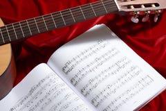 Gitary akustycznej i muzyki notatki na czerwonej aksamitnej tkaninie, zamknięty widok przedmioty Obraz Royalty Free