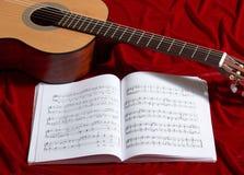 Gitary akustycznej i muzyki notatki na czerwonej aksamitnej tkaninie, zamknięty widok przedmioty Obraz Stock