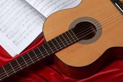 Gitary akustycznej i muzyki notatki na czerwonej tkaninie, zamknięty widok obj Zdjęcia Stock