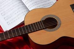 Gitary akustycznej i muzyki notatki na czerwonej tkaninie, zamknięty widok przedmioty Zdjęcie Stock