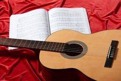 Gitary akustycznej i muzyki notatki na czerwonej tkaninie, zamknięty widok przedmioty Fotografia Stock