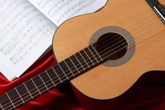 Gitary akustycznej i muzyki notatki na czerwonej tkaninie, zamknięty widok przedmioty Obraz Royalty Free