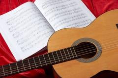Gitary akustycznej i muzyki notatki na czerwonej tkaninie, zamknięty widok przedmioty Zdjęcia Royalty Free