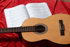 Gitary akustycznej i muzyki notatki na czerwonej tkaninie, zamknięty widok przedmioty Zdjęcie Royalty Free