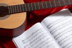 Gitary akustycznej i muzyki notatki na czerwonej tkaninie, zamknięty widok przedmioty Obrazy Stock