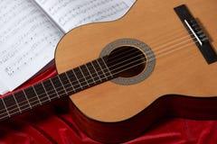 Gitary akustycznej i muzyki notatki na czerwonej tkaninie, zamknięty widok przedmioty Obraz Stock