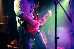 Gitarzysta bawić się elektryczną gitarę na rockowej drynduli Obrazy Stock