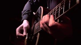 Gitarzysta Bawić się gitarę akustyczną na scenie - Zamyka W górę Strumming, muzyka na żywo zbiory