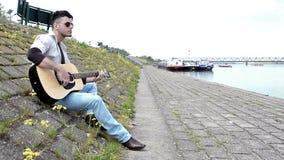 Gitarzysta bawić się gitarę blisko rzeki zdjęcie wideo