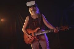 Gitarzysta doświadcza VR szkła podczas gdy wykonujący w klubie nocnym obraz stock