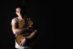 Gitarzysta, muzyka Młodego człowieka stojaki z gitarą akustyczną na czarnym odosobnionym tle Horyzontalna rama zdjęcie royalty free