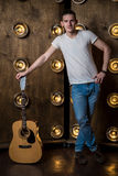 Gitarzysta, muzyka Młodego człowieka stojaki z gitarą akustyczną w tle z światłami za on Vertical rama fotografia stock
