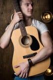 Gitarzysta, muzyka Młodego człowieka stojaki z gitarą akustyczną w tle z światłami za on Vertical rama obrazy royalty free