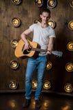 Gitarzysta, muzyka Młody człowiek bawić się gitarę akustyczną na tle z światłami za on Vertical rama obraz stock