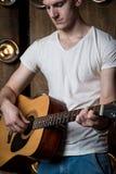 Gitarzysta, muzyka Młody człowiek bawić się gitarę akustyczną na tle z światłami za on Vertical rama fotografia stock