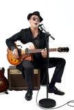 Gitarzysta śpiewa obsiadanie na amplifikatorze Zdjęcia Royalty Free