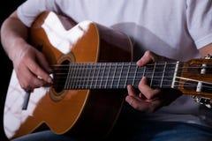 Gitarzysta ręki bawić się klasyczną gitarę Obrazy Stock