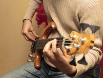 Gitarzysta siedzi basową gitarę i bawić się Obraz Stock