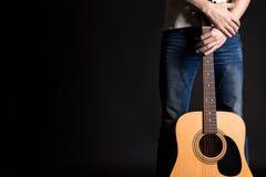 Gitarzysta trzyma dwa ręki z gitarą akustyczną na czarnym odosobnionym tle obrazy stock