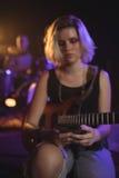 Gitarzysta używa wiszącą ozdobę w klubie nocnym podczas gdy siedzący zdjęcie stock