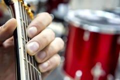 Gitarzysty ` s ręka zakończenie i miękka ostrość, bierze akrod na gitary fretboard, przeciw tłu bębenu set Zdjęcie Royalty Free
