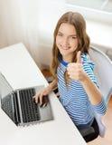 Gitl adolescente sonriente con el ordenador portátil en casa Fotografía de archivo libre de regalías
