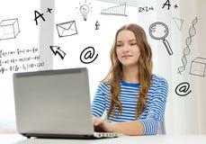Gitl adolescente sonriente con el ordenador portátil en casa Imagen de archivo libre de regalías