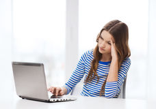 Gitl adolescente trastornado con el ordenador portátil en casa Imagen de archivo