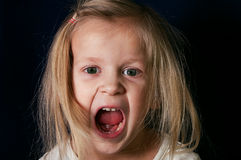 Gitl Screaming. Little girl screaming with open mouth, emotional horizontal studio shot Royalty Free Stock Photos