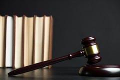 Giudichi il martelletto accanto al mucchio dei libri su fondo di legno Fotografie Stock Libere da Diritti