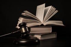 Giudichi il martelletto accanto al mucchio dei libri su fondo di legno Immagini Stock Libere da Diritti