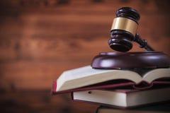 Giudichi il martelletto del ` s sopra il mucchio dei libri di legge Immagine Stock