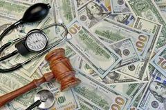 Giudici Gavel e strumenti medici sul fondo dei contanti del dollaro Immagine Stock