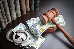 Giudici Gavel, manette, contanti del dollaro e libro sulla Tabella nera Immagine Stock