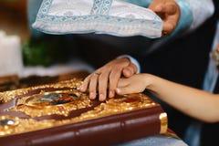 Giuramento alle persone appena sposate sulla bibbia luxuriously decorata, sulle mani degli uomini e sulle donne nella chiesa vici Fotografia Stock