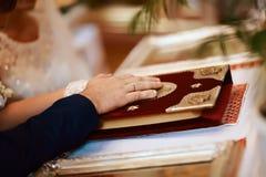 Giuramento alle persone appena sposate sulla bibbia luxuriously decorata, sulle mani degli uomini e sulle donne nella chiesa vici Fotografie Stock Libere da Diritti