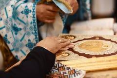 Giuramento alle persone appena sposate sulla bibbia luxuriously decorata, sulle mani degli uomini e sulle donne nella chiesa vici Immagini Stock Libere da Diritti