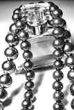 Give. Black tahitian pearls draped over a bottle of perfume royalty free stock photography