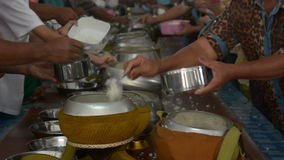 Give alms of rice to a Buddhist monk in temple stock video footage