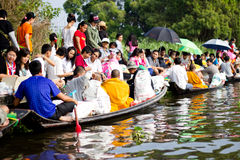 Give alms to a Buddhist monk on boat Royalty Free Stock Images